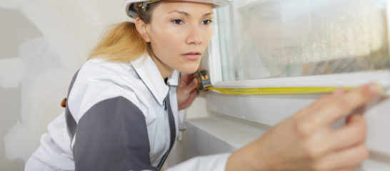 female builder measuring a window